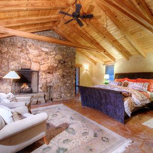 Пример оригинального дизайна: большая хозяйская спальня с желтыми стенами, полом из терракотовой плитки, стандартным камином и фасадом камина из камня