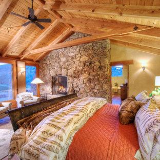 Diseño de dormitorio principal, de estilo americano, grande, con paredes amarillas, chimenea tradicional y marco de chimenea de piedra