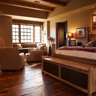 Modelo de dormitorio principal, rústico, de tamaño medio, con paredes beige, suelo de madera en tonos medios, marco de chimenea de yeso y chimenea de esquina