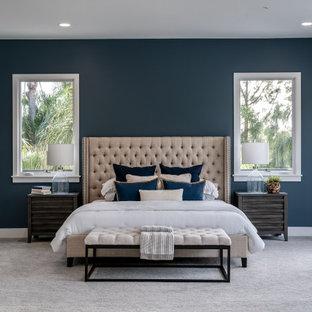 Geräumiges Mediterranes Hauptschlafzimmer mit blauer Wandfarbe, Teppichboden, Kamin, gefliester Kaminumrandung und grauem Boden in San Diego