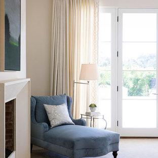 Ejemplo de dormitorio principal, tradicional renovado, de tamaño medio, con paredes beige, moqueta, chimenea tradicional, marco de chimenea de hormigón y suelo beige
