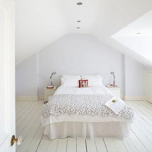 Nordisches Schlafzimmer ohne Kamin mit blauer Wandfarbe, gebeiztem Holzboden und weißem Boden in Dublin