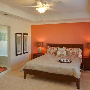 Inredning av ett exotiskt stort huvudsovrum, med orange väggar och heltäckningsmatta