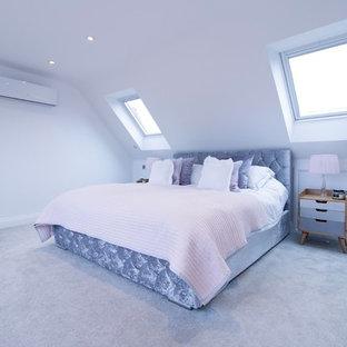 Ejemplo de dormitorio principal, actual, grande, con paredes blancas, moqueta, estufa de leña, marco de chimenea de metal y suelo gris