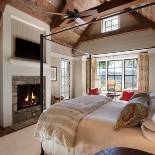 This is an example of a country bedroom in Other with a standard fireplace and a stone fireplace surround.