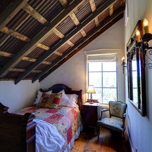 Foto de dormitorio tipo loft, rural, pequeño, con paredes beige y suelo de madera en tonos medios
