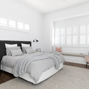 Design ideas for a transitional guest bedroom in Brisbane with white walls, medium hardwood floors, no fireplace and brown floor.