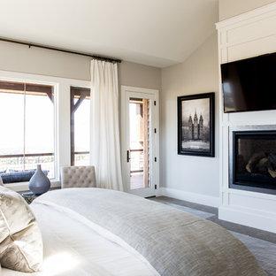 Ejemplo de dormitorio principal, campestre, grande, con paredes beige, moqueta, chimenea tradicional y marco de chimenea de metal