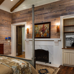Diseño de dormitorio principal, rural, de tamaño medio, con paredes marrones, suelo de madera oscura, chimenea tradicional, marco de chimenea de hormigón y suelo marrón