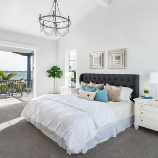 Example of a large beach style master carpeted, gray floor and exposed beam bedroom design in Tampa with blue walls