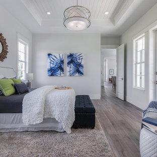 Großes Maritimes Hauptschlafzimmer mit grauer Wandfarbe, hellem Holzboden und Holzdielendecke in Tampa
