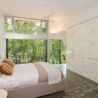 Стильный дизайн: хозяйская спальня в современном стиле с белыми стенами и бетонным полом - последний тренд