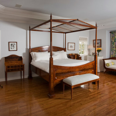 Example of a classic master medium tone wood floor bedroom design in Orange County with gray walls and no fireplace