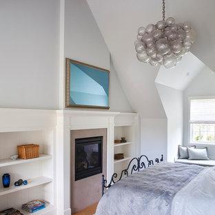 Ejemplo de dormitorio principal, tradicional renovado, grande, con paredes grises, suelo de linóleo, chimenea de doble cara y marco de chimenea de piedra