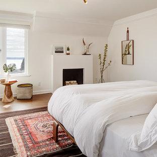На фото: спальня в стиле ретро с белыми стенами, темным паркетным полом, фасадом камина из штукатурки и коричневым полом с