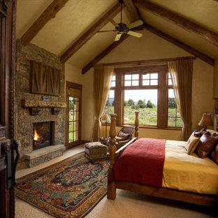 Foto de dormitorio principal, rural, grande, con paredes beige, moqueta, chimenea tradicional, marco de chimenea de piedra y suelo beige