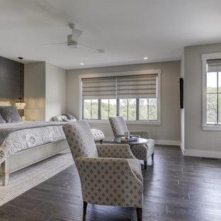 シカゴの大きいカントリー風おしゃれな主寝室 (グレーの壁、濃色無垢フローリング、横長型暖炉、漆喰の暖炉まわり、茶色い床)