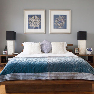 Design ideas for a beach style bedroom in Singapore with grey walls and medium hardwood floors.