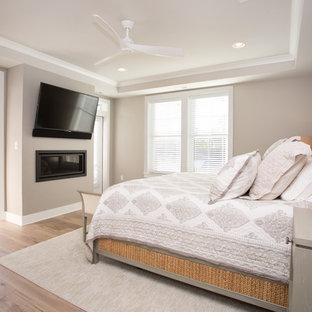 Ejemplo de dormitorio principal, marinero, grande, con paredes beige, suelo de madera clara, chimenea lineal y suelo beige