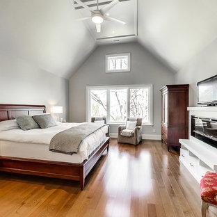 Свежая идея для дизайна: большая хозяйская спальня в классическом стиле с серыми стенами, паркетным полом среднего тона, подвесным камином, фасадом камина из штукатурки и коричневым полом - отличное фото интерьера