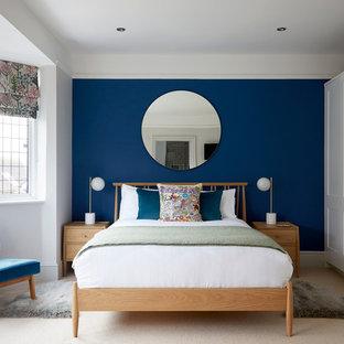 Cette image montre une chambre traditionnelle avec un mur bleu, aucune cheminée et un sol beige.