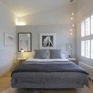 Modelo de dormitorio principal, contemporáneo, de tamaño medio, sin chimenea, con paredes blancas, suelo de madera clara y suelo beige