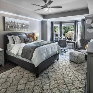 Imagen de habitación de invitados actual, de tamaño medio, con paredes grises, suelo laminado y suelo marrón