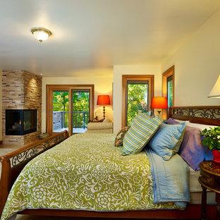 Foto de dormitorio principal, de estilo americano, grande, con paredes beige, moqueta, chimenea de esquina y marco de chimenea de piedra
