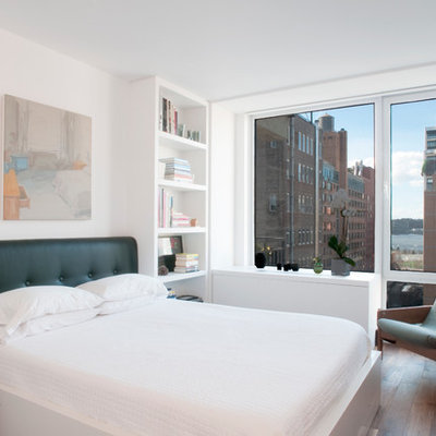 Example of a trendy loft-style medium tone wood floor bedroom design in New York with white walls