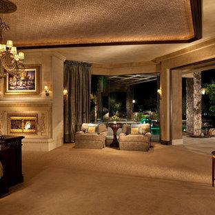 Cette photo montre une grand chambre chic avec un mur beige, une cheminée standard et un manteau de cheminée en pierre.