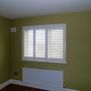 ダブリンの中サイズのコンテンポラリースタイルのおしゃれな客用寝室 (黄色い壁、ラミネートの床、茶色い床) のインテリア