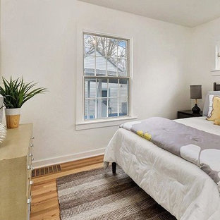Example of a small midcentury modern guest light wood floor and red floor bedroom design in Boise with white walls