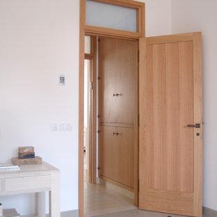 Diseño de dormitorio principal, actual, grande, con paredes blancas, suelo de piedra caliza y suelo beige