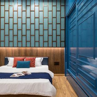 他の地域のコンテンポラリースタイルのおしゃれな寝室 (青い壁、無垢フローリング、茶色い床) のレイアウト