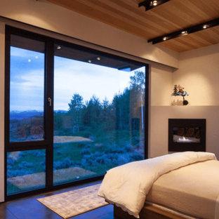 他の地域の中くらいのコンテンポラリースタイルのおしゃれな寝室 (ベージュの壁、コンクリートの床、コーナー設置型暖炉、漆喰の暖炉まわり、茶色い床) のレイアウト