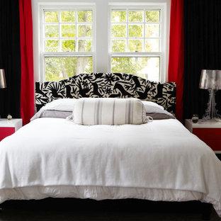 Esempio di una camera matrimoniale minimal di medie dimensioni con pareti nere, moquette, camino classico e cornice del camino in mattoni