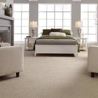 Пример оригинального дизайна: хозяйская спальня в стиле модернизм с серыми стенами, ковровым покрытием, стандартным камином и фасадом камина из дерева