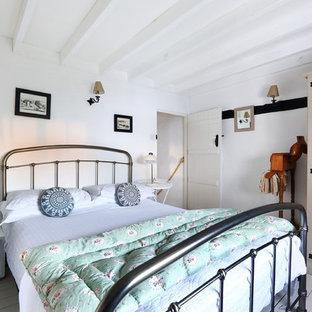 サセックスの小さいカントリー風おしゃれな主寝室 (白い壁、塗装フローリング、標準型暖炉、レンガの暖炉まわり) のレイアウト
