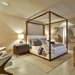 ロサンゼルスの広いトロピカルスタイルのおしゃれな客用寝室 (ベージュの壁、暖炉なし、磁器タイルの床、石材の暖炉まわり、ベージュの床)
