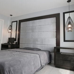 Example of a mid-sized trendy master laminate floor and gray floor bedroom design in DC Metro with gray walls