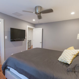 Example of a small trendy master medium tone wood floor bedroom design in DC Metro with gray walls and no fireplace