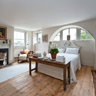 This is an example of a large traditional bedroom in London with medium hardwood flooring, a standard fireplace, a tiled fireplace surround and beige floors.