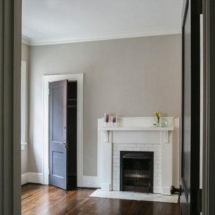 Imagen de habitación de invitados de estilo americano, de tamaño medio, con suelo de madera oscura, chimenea tradicional y marco de chimenea de baldosas y/o azulejos