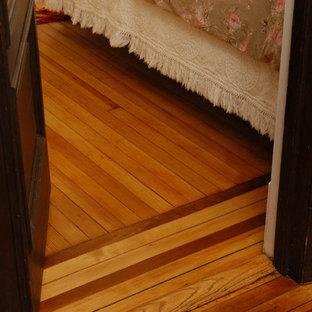 Modelo de dormitorio principal, clásico, de tamaño medio, con paredes blancas, suelo de madera clara, chimenea tradicional y marco de chimenea de ladrillo