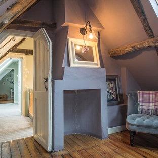 Imagen de habitación de invitados de estilo de casa de campo, pequeña, con suelo de madera en tonos medios, chimenea de esquina, marco de chimenea de hormigón y paredes púrpuras