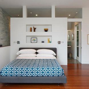 Cette image montre une chambre parentale vintage avec un mur blanc et un sol en bois brun.