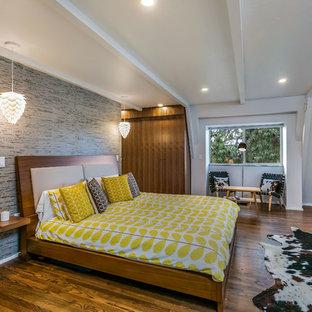 Inspiration pour une chambre parentale design avec un mur blanc, un sol en bois brun et un poêle à bois.