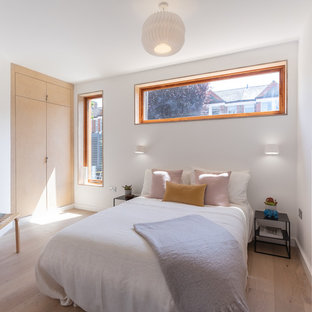 Medium sized contemporary master bedroom in London with white walls, light hardwood flooring and beige floors.