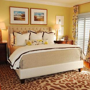 Imagen de dormitorio principal, bohemio, de tamaño medio, sin chimenea, con paredes amarillas, suelo de madera en tonos medios y suelo marrón