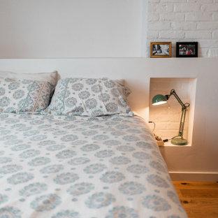 Cette photo montre une chambre parentale tendance de taille moyenne avec un mur blanc, un sol en bois clair et un mur en parement de brique.